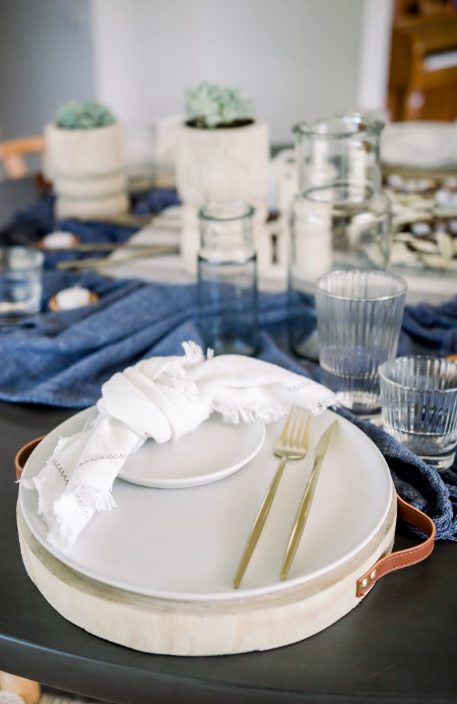 place setting with white dinnerware and brushed gold flatware