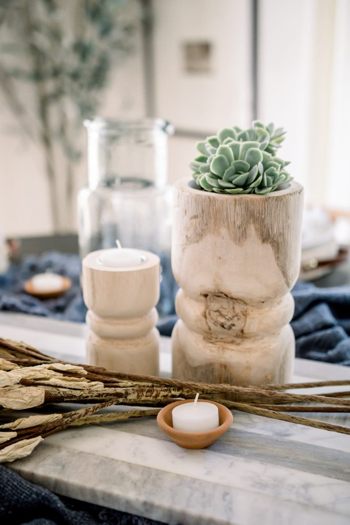 succulent and candle pillars with tealights on marble charcuterie board