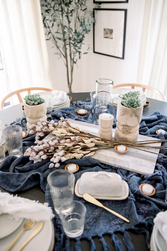 blue table throw on dining room table with place setting; how to style a throw blanket