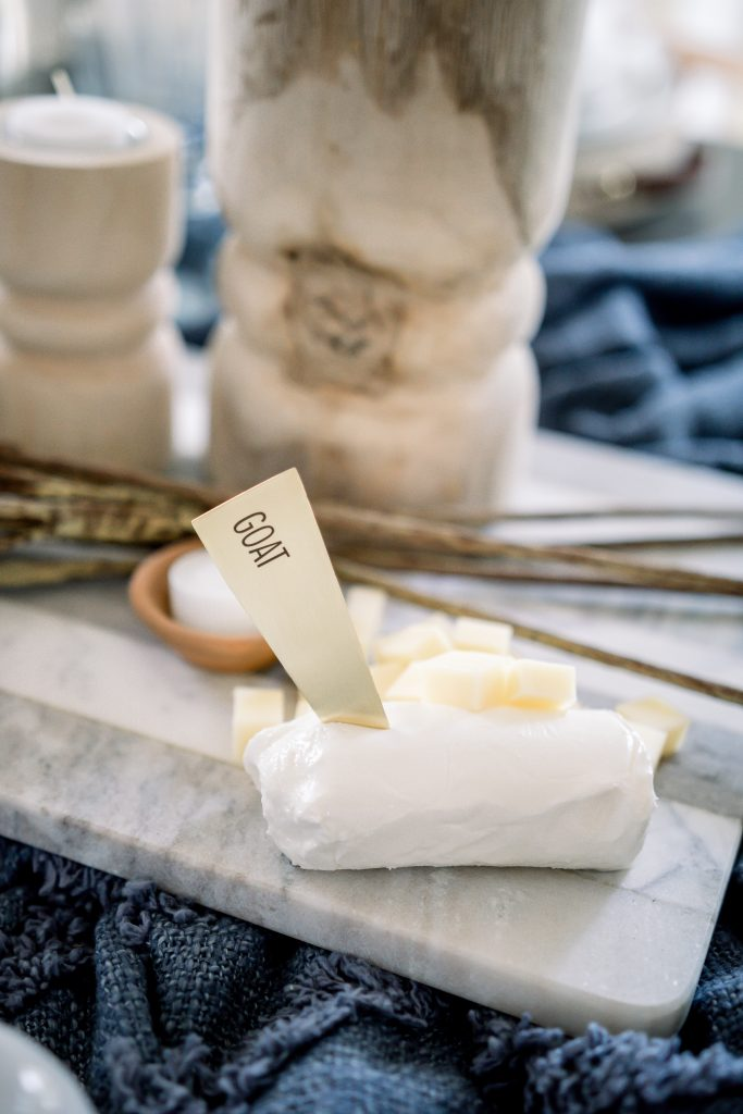 brass cheese marker pressed into a block of goat cheese on marble cutting board