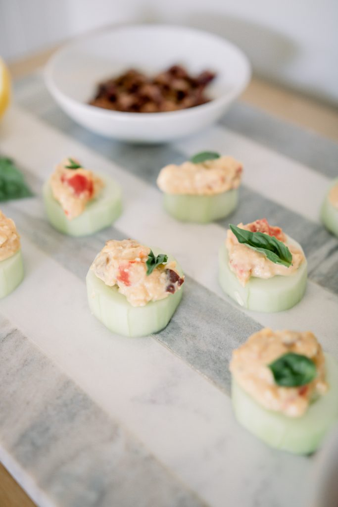 cucumber and hummus bites on a striped marble charcuterie board