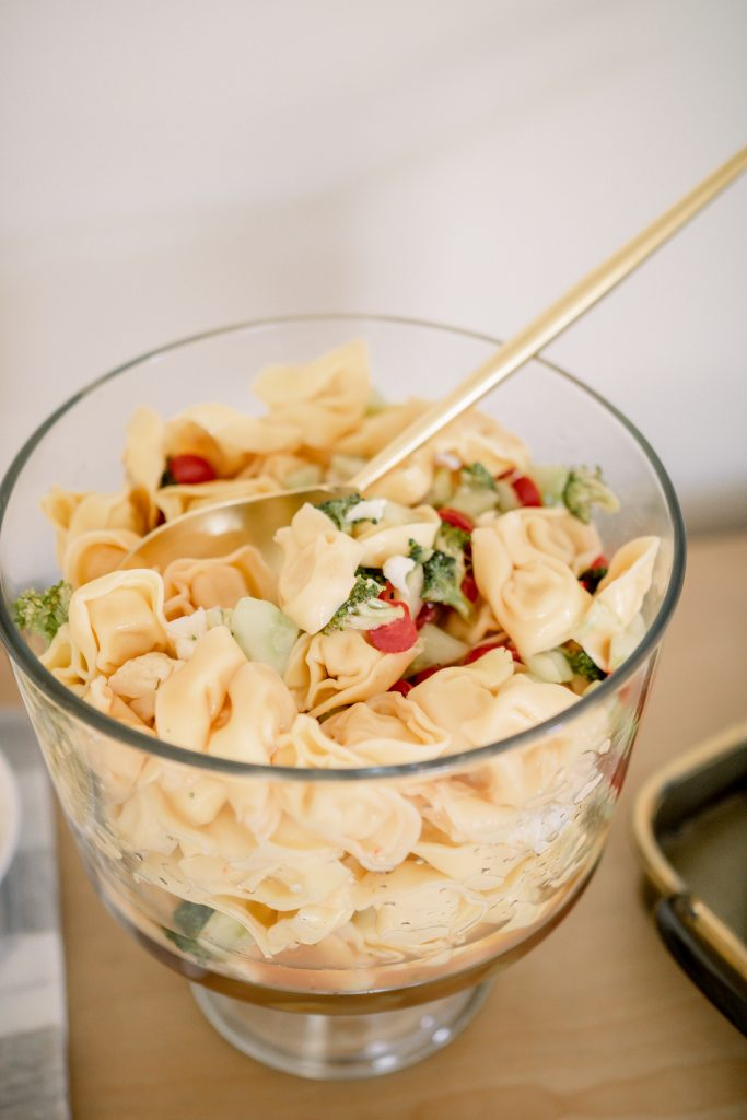 tortellini salad in a glass serving bowl with gold serveware spoon