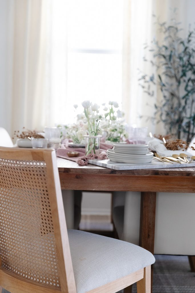 a dining room table set with a pink table throw and white flowers