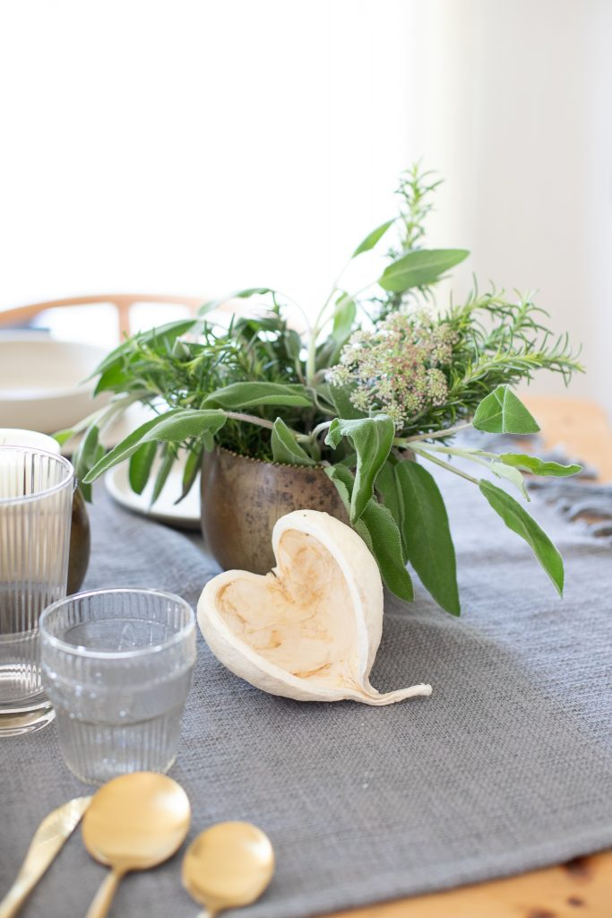 dried natural buddha nut with greenery and candles as a centerpiece medley