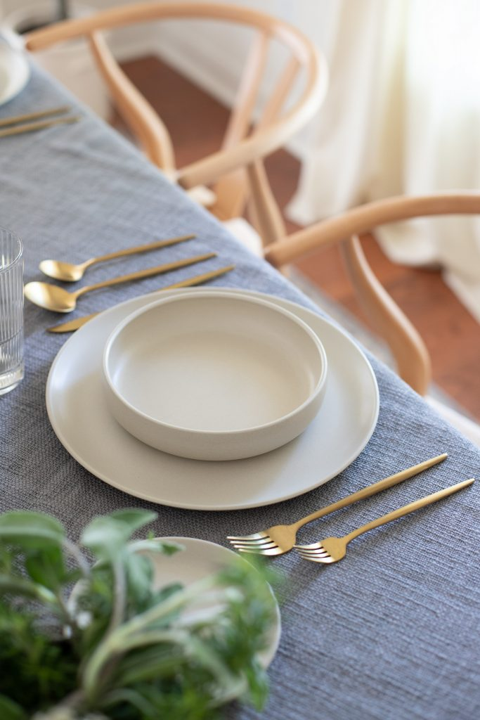 pita dinnerware with brushed gold flatware on steel colored table throw blanket