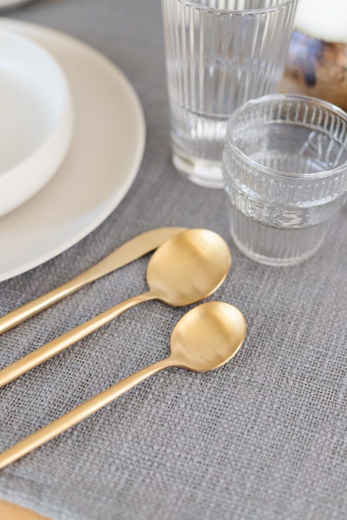 brushed gold flatware with white dinner plates and clear glass tumblers