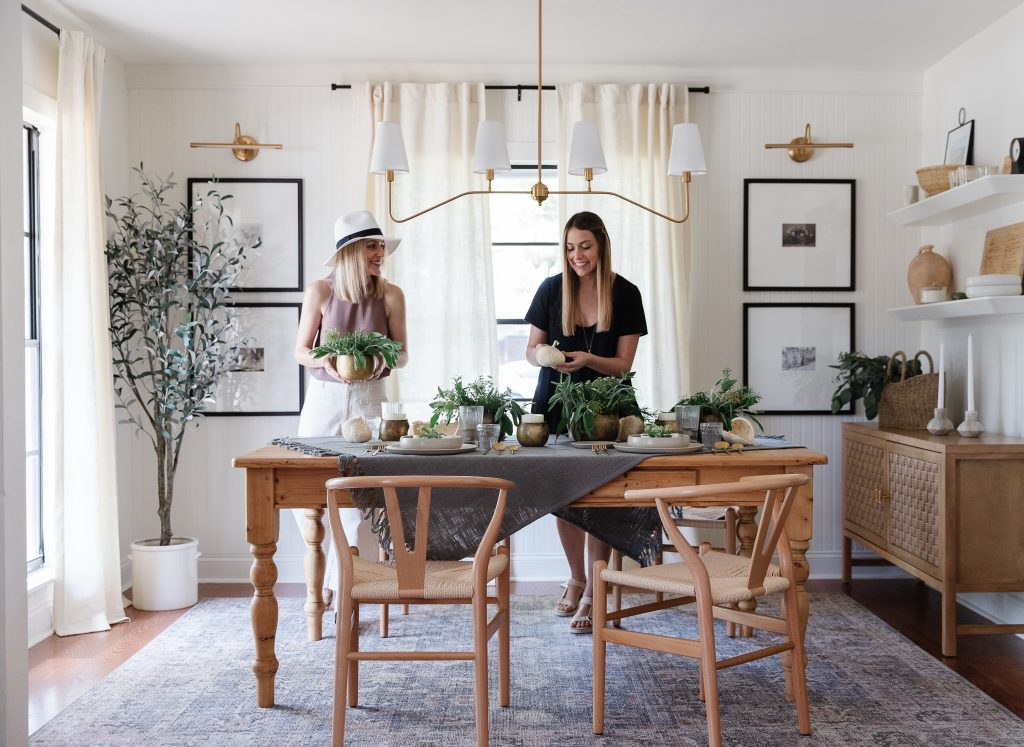 two women setting a Summer Soiree Tablescape in dining room