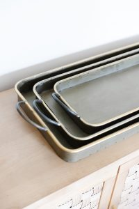 galvanized metal tray with gold rim on a sideboard