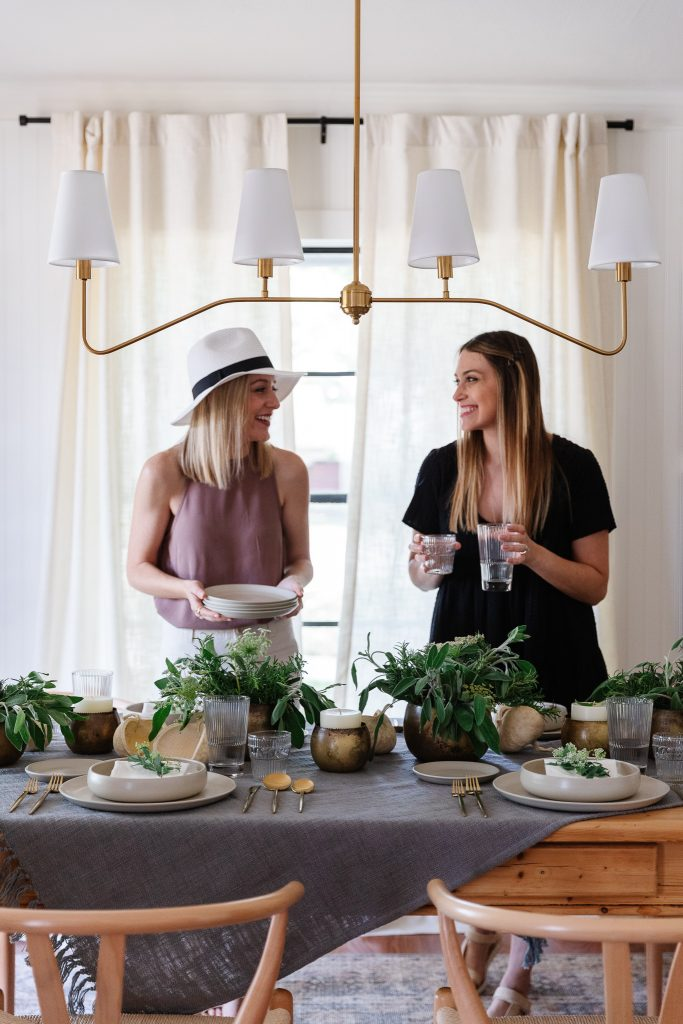 two women smiling and setting dining room table