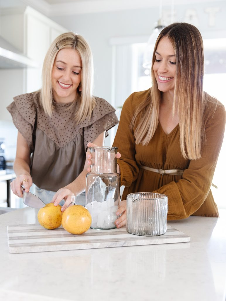 a woman cutting a grapefruit while another holds a clear pitcher on a kitchen counter top