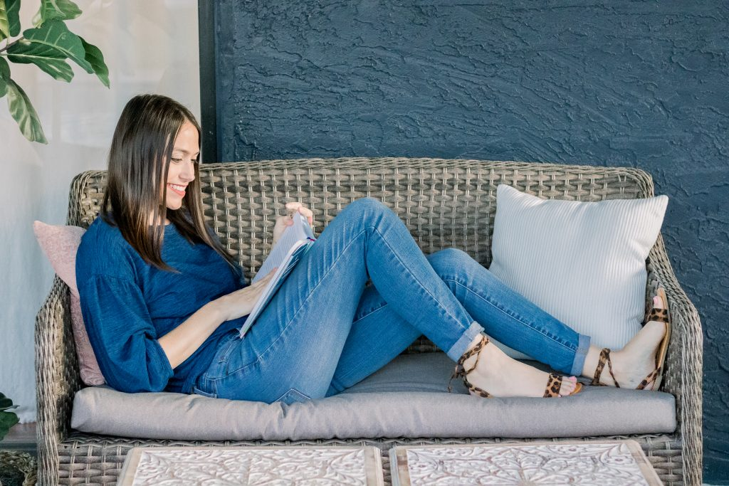 achieving happiness through inviting loved ones in; woman reclining on outdoor patio sofa