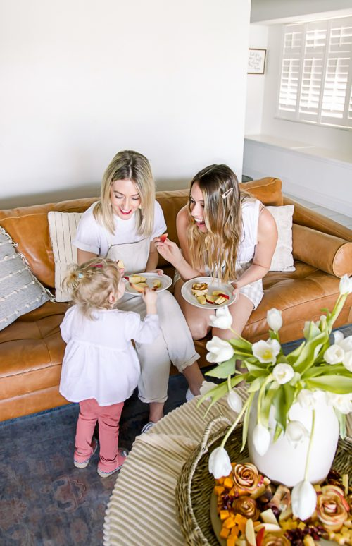 two women and toddler sitting on brown leather couch