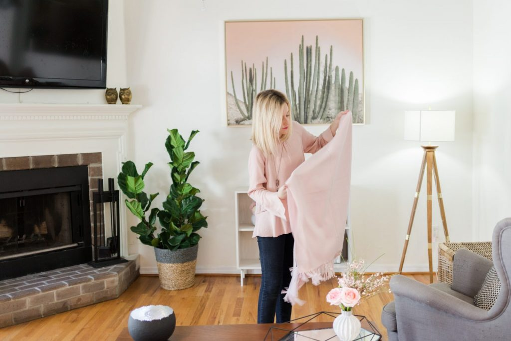 clean your home, woman folding a pink blanket in living room with fireplace