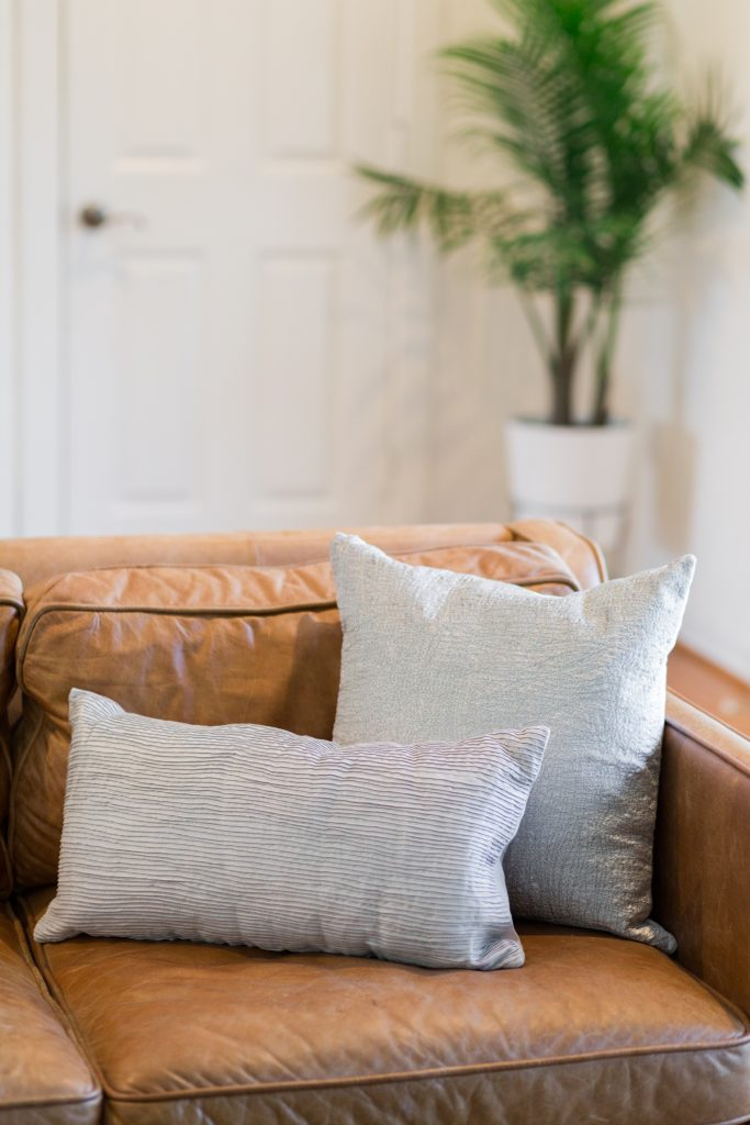 basket hostful hack for after guests leave; leather couch with neutral pillows