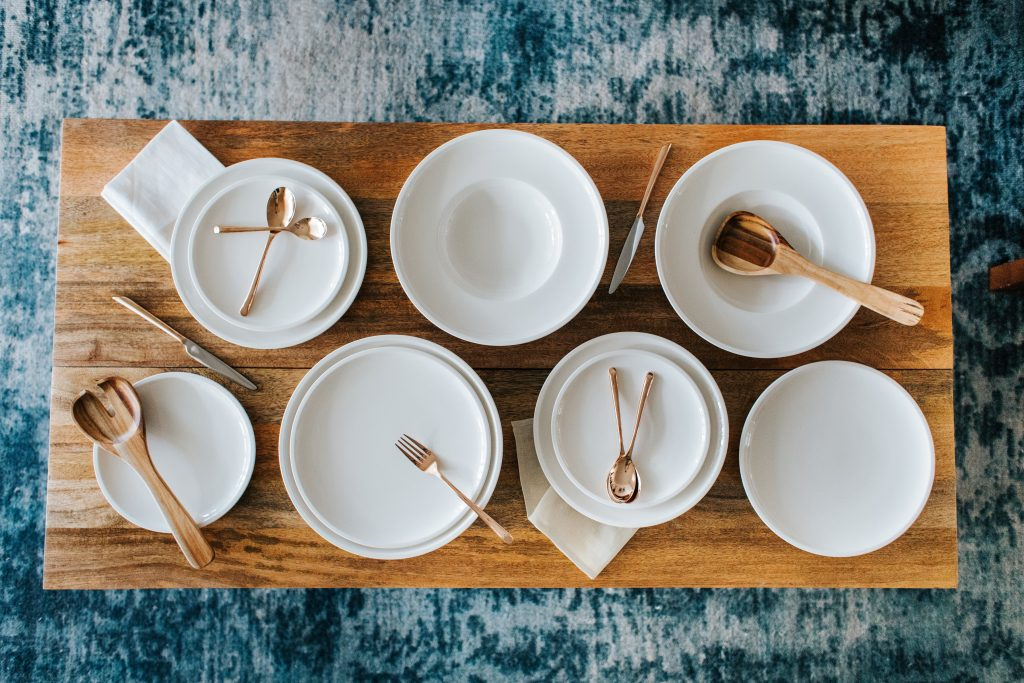 white dinner plates and bowls with gold flatware on a wooden board for having people over