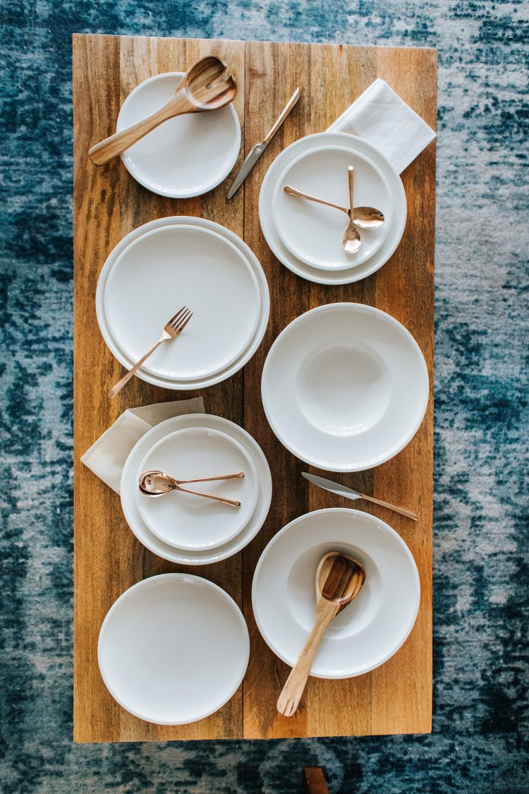 white dinner plates and bowls with gold flatware on a wooden board