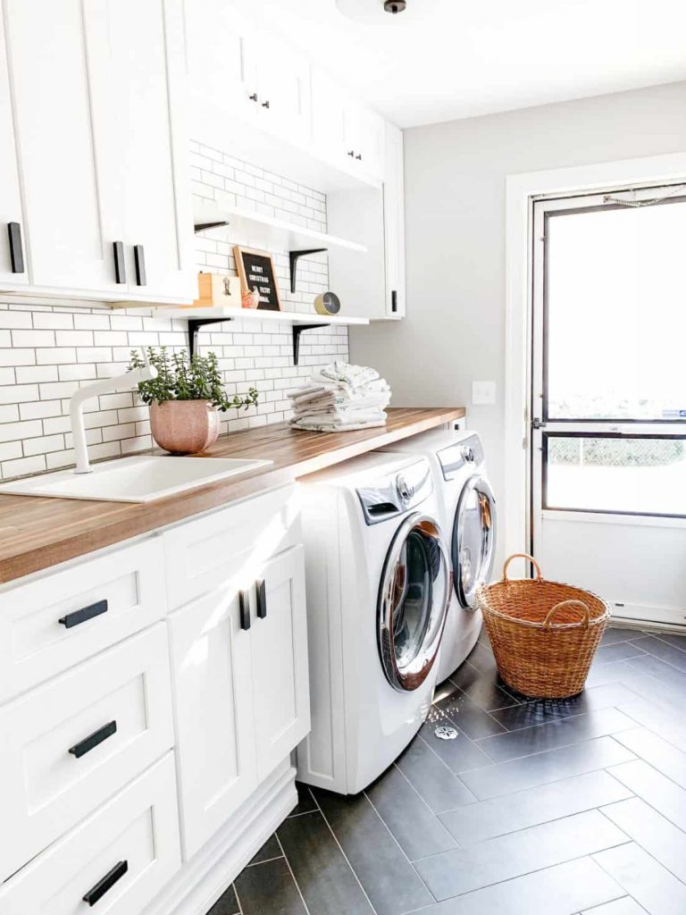 clean home with white washer and dryer in a laundry room with a basket sitting on floor