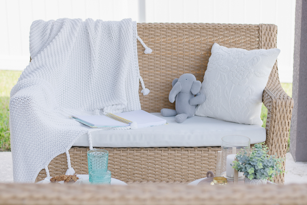 white throw blanket with tassels on outdoor seating on porch; how to style a throw blanket