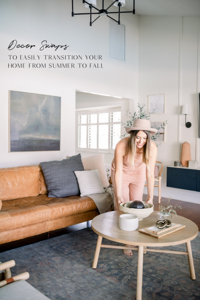 brunette woman with light beige hat on placing decorative bowl onto coffee table; summer to fall decor swaps