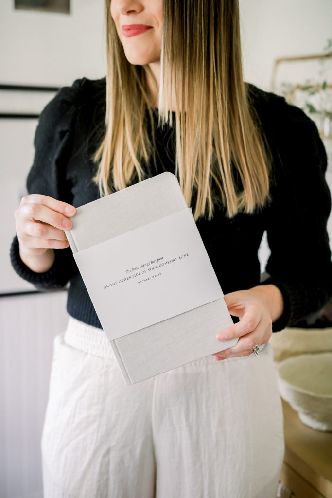 brunette woman in black sweater and white linen pants holding a Full Focus Planner box