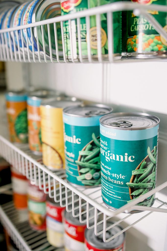 canned vegetables on white wire shelving in pantry as pantry staples