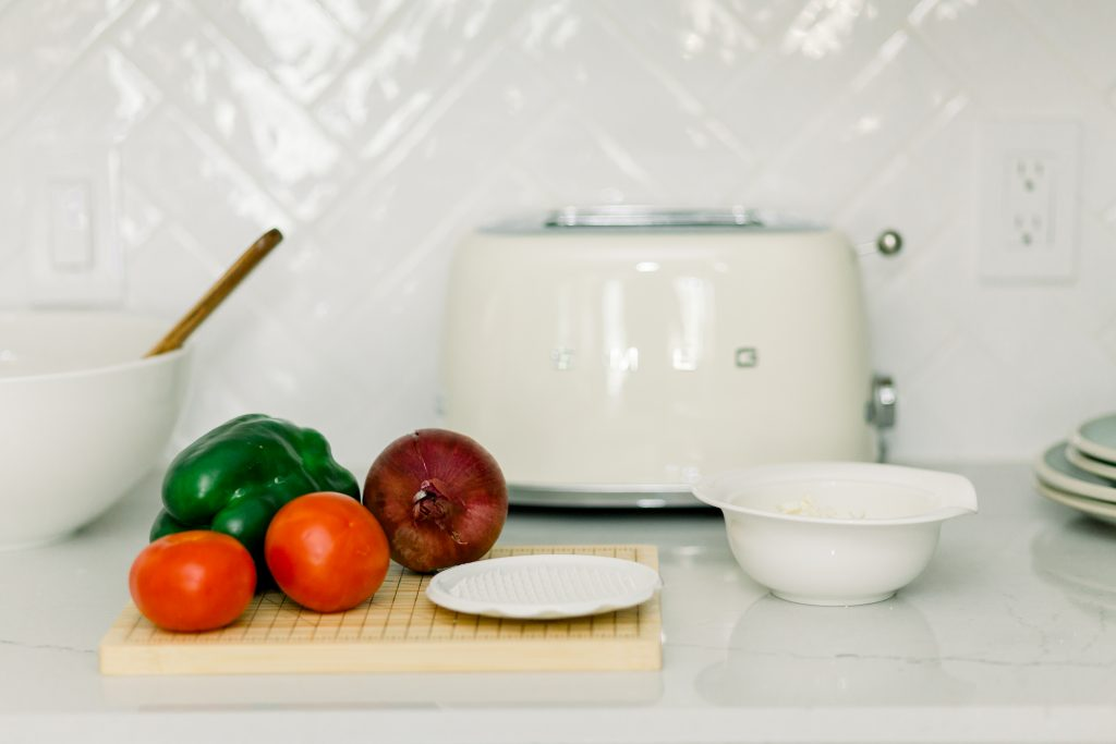 keep kitchen clean with scrap bowl hack; white kitchen counter top with natural wood cutting board with tomatoes, green bell pepper and onion next to white mixing bowls; white toaster in background; white backsplash