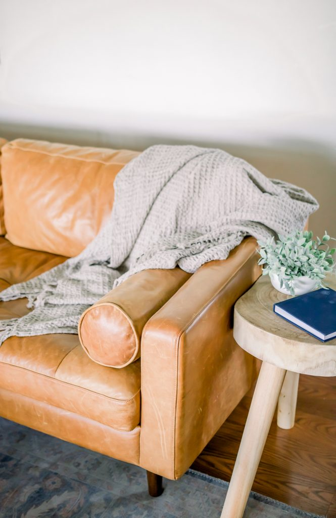 silver waffle throw blanket on leather couch; how to style a throw blanket
