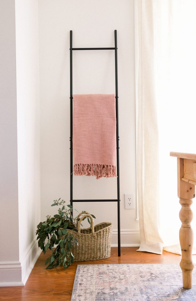 how to style a throw blanket; blush pink rose blanket on black ladder in dining room