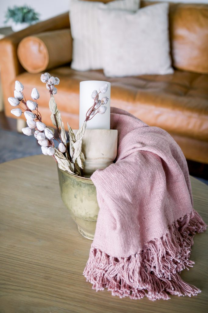 pink throw blanket in large planter with candle and faux greenery