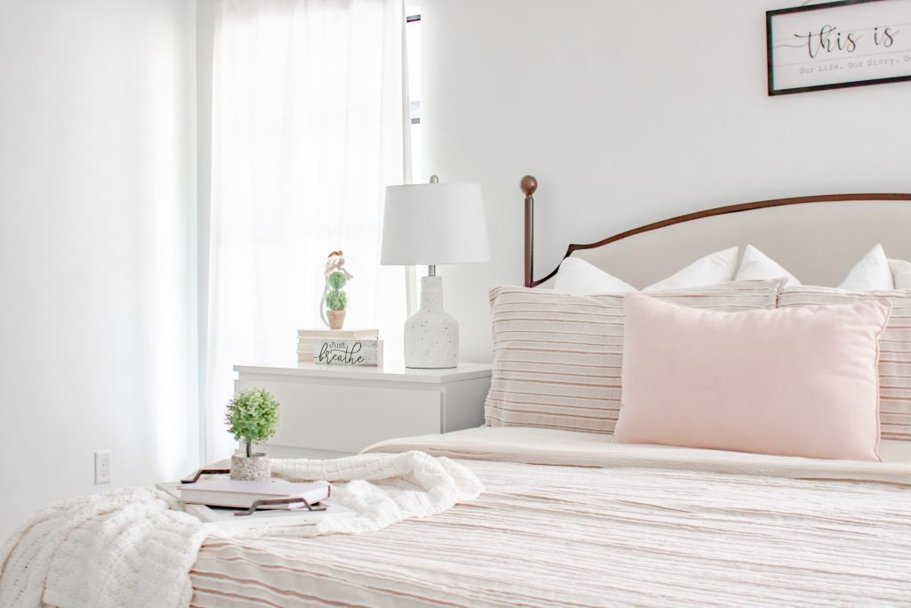white blanket on guestroom bed with blush pink pillows; how to style a throw blanket