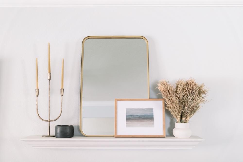 candelabrum, mirror, candle and dried greenery on white shelf