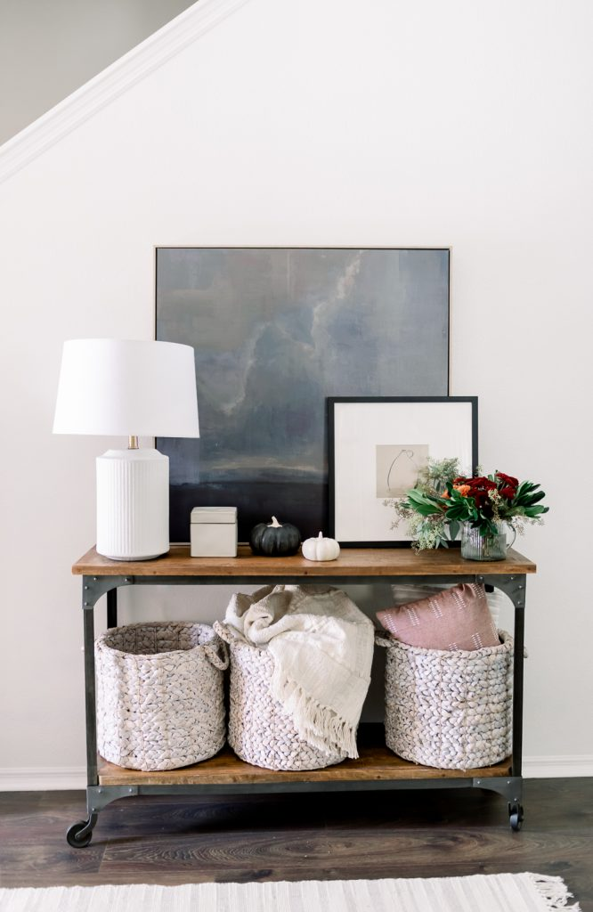 summer to fall foyer decor swaps; foyer side table with white lamp, artwork, and cream colored baskets