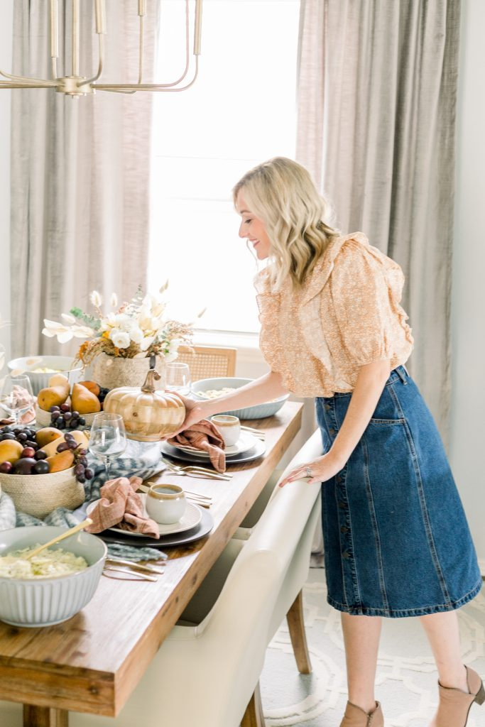 create a menu for everyone; a woman setting a thanksgiving tablescape