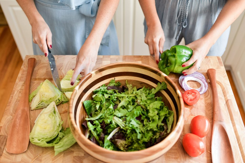 create a menu that fits every guest's taste; two women making a salad on a kitchen island